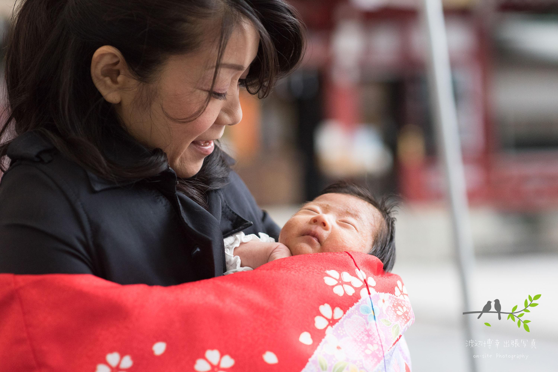 お宮参りの掛着姿で赤ちゃんを抱く母親