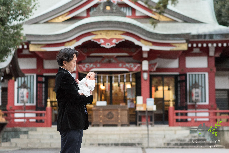 神社本殿の前で赤ちゃんを抱き立つ父親