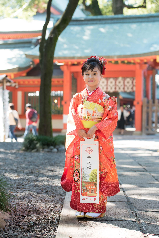 千歳飴を持ち立っているオレンジの着物を着た女の子