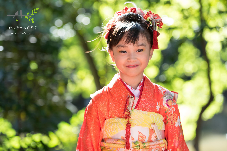 明るい林の前に立つオレンジの着物を着た七五三の女の子