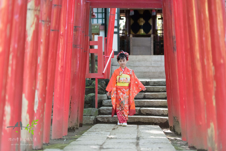 赤い鳥居の下に立つオレンジの着物を着た女の子
