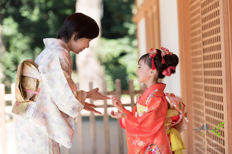 両手を使って遊ぶオレンジの着物を着た女の子の横顔