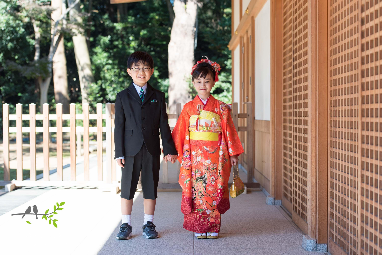 オレンジの着物を着た女の子と手をつなぐ男の子
