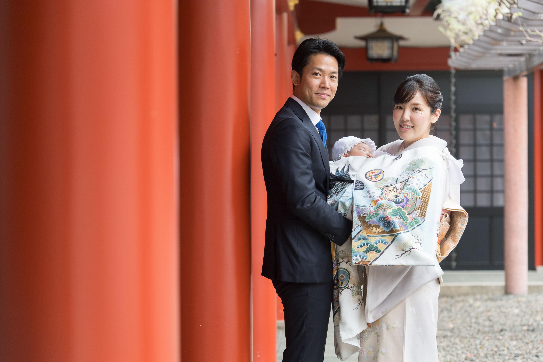 赤く並ぶ柱の横で掛着姿の赤ちゃんを抱き立つ和装の女性と男性