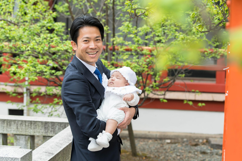 赤ちゃんを抱き微笑む男性