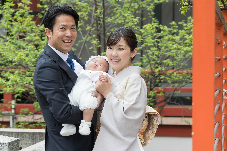 赤ちゃんを抱き微笑む男性と和装姿の女性