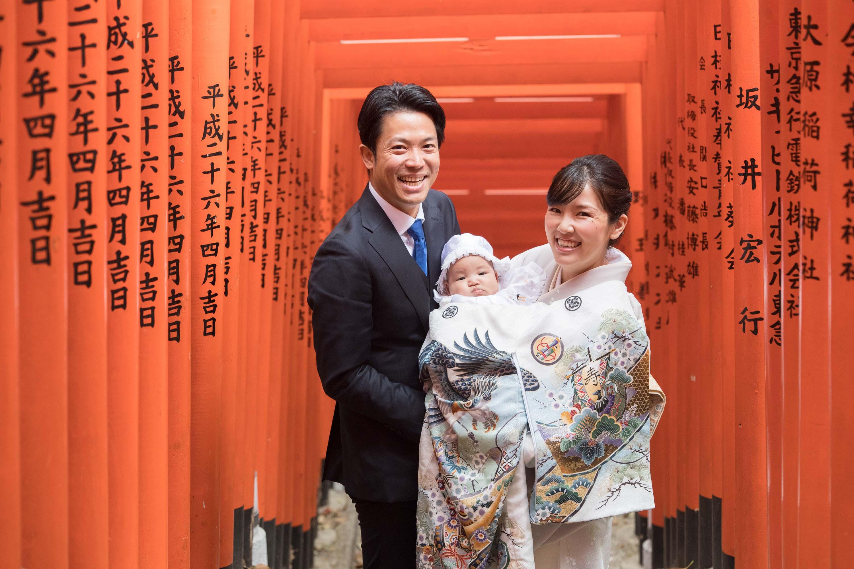 赤い沢山並んだ鳥居の下で赤ちゃんを抱く和装の女性と横に立つ男性