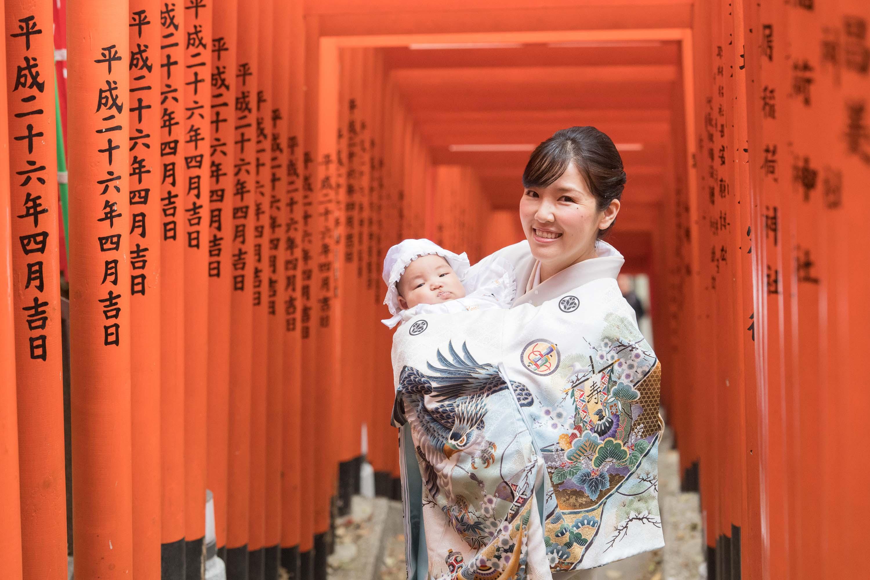 赤い沢山並んだ鳥居の下で赤ちゃんを抱く微笑む和装の女性