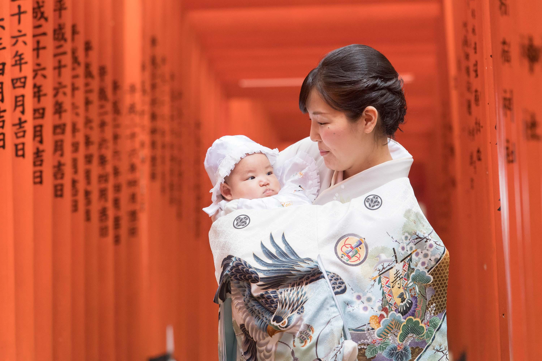 赤い沢山並んだ鳥居の下で赤ちゃんを抱く和装の女性
