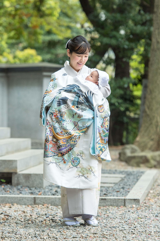 掛着姿の赤ちゃんを抱く微笑む立っている和装の女性