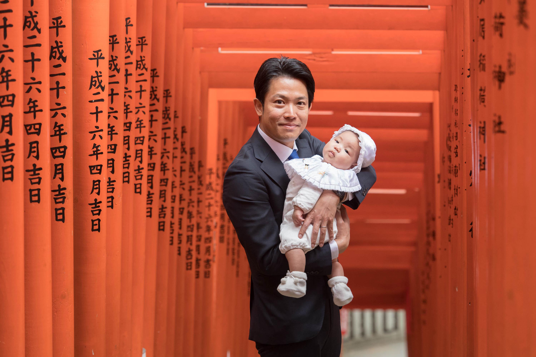 赤い沢山並んだ鳥居の下で赤ちゃんを抱くスーツ姿の男性