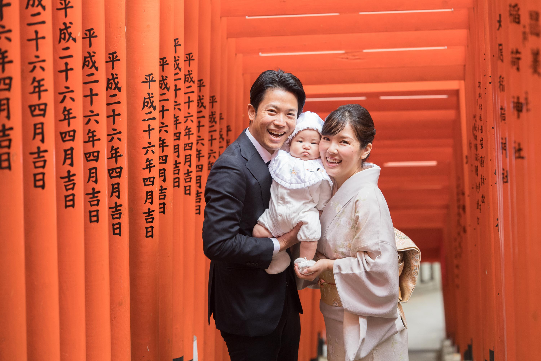 赤い沢山並んだ鳥居の下で赤ちゃんを抱く和装の女性と男性