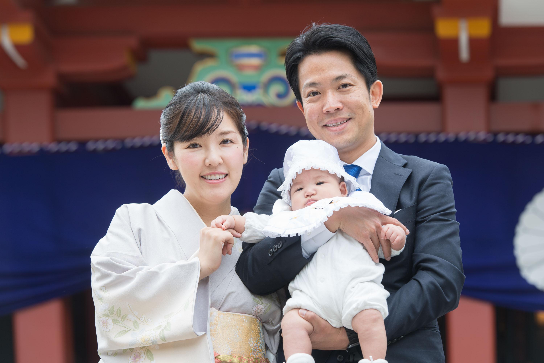 赤い神社の門の前で赤ちゃんを抱く女性と男性
