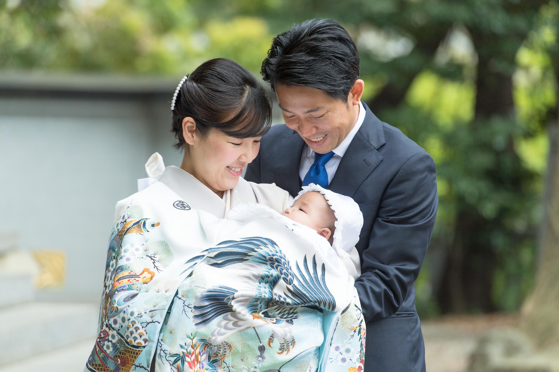 掛着姿の赤ちゃんを抱いている和装の女性とよりそう男性