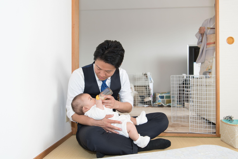 あぐらをかいて赤ちゃんを抱きミルクを飲ませる男性