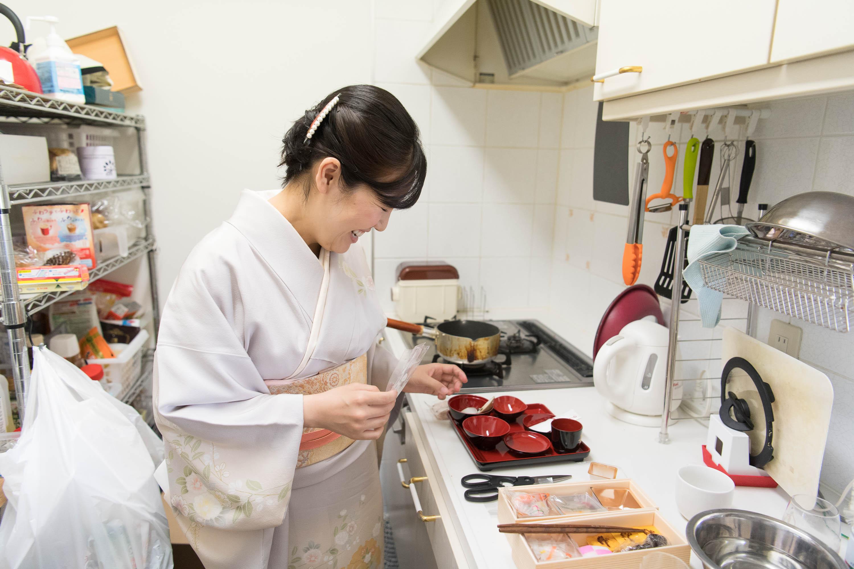 料理の用意をする和装の女性