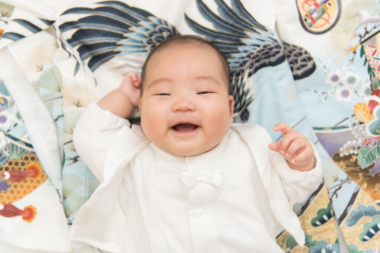上から見た白い掛着を着た笑う赤ちゃん