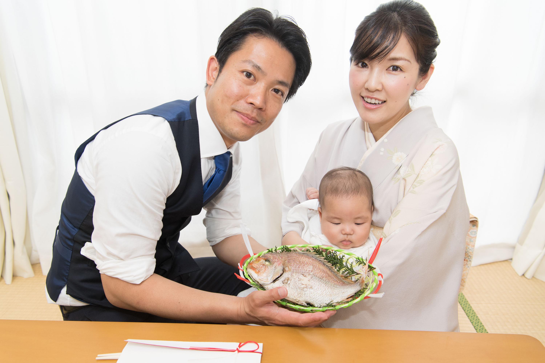 赤ちゃんを抱く和装の女性と鯛を持つ男性