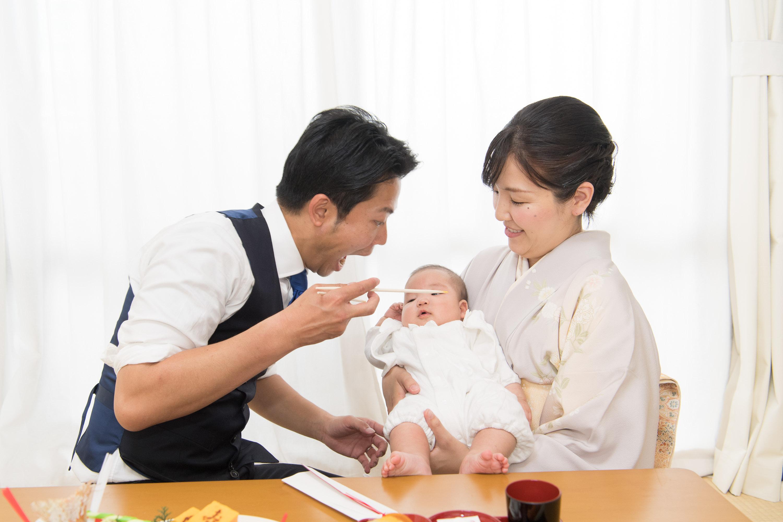 赤ちゃんを抱く和装の女性と横にいる男性