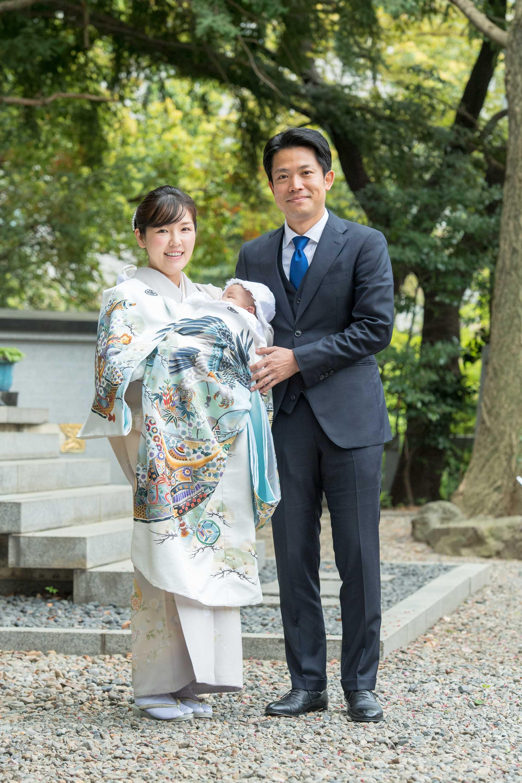 掛着姿の赤ちゃんを抱く微笑む和装の女性と横に立つ男性