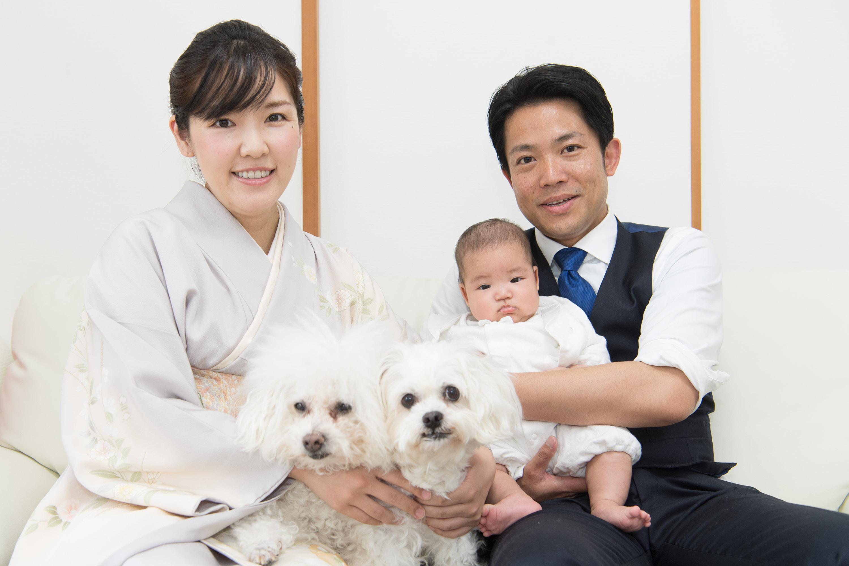 赤ちゃんを抱く男性と和装の女声と2匹の白い犬