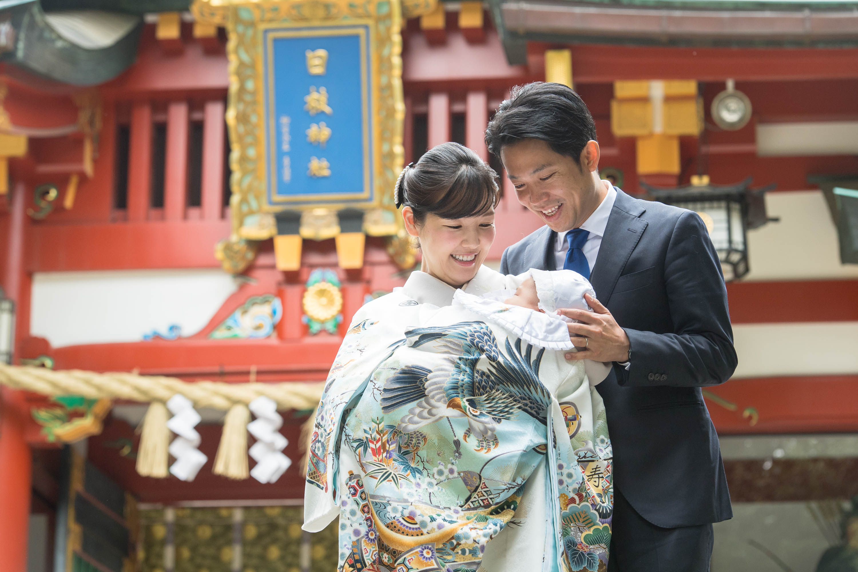 赤い神社の門の前で掛着姿の赤ちゃんを抱く微笑む和装の女性と寄り添う男性