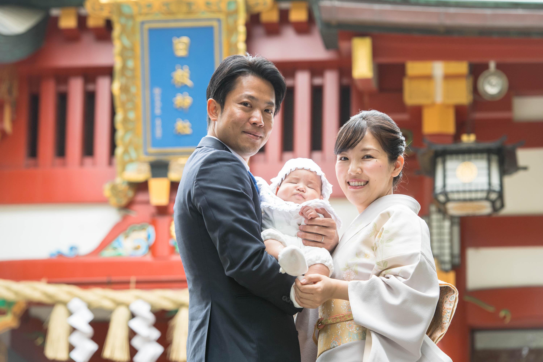 赤い神社の門の前で掛着姿の赤ちゃんを抱く和装の女性と寄り添う男性