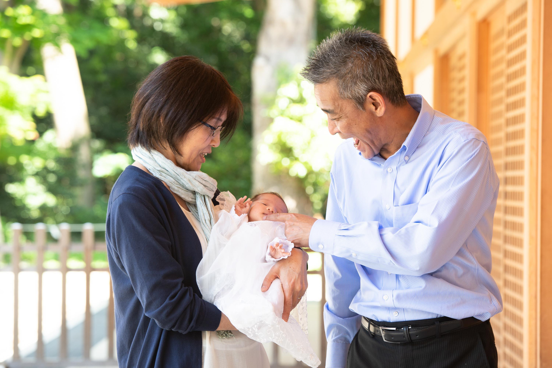赤ちゃんを抱く女性と横でほっぺたを触る男性