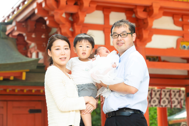 赤い神社門も前で赤ちゃんを抱く女性と男性