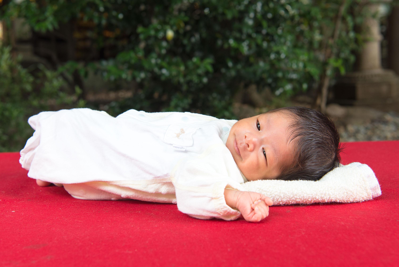 赤い縁台の上に寝転ぶ赤ちゃん