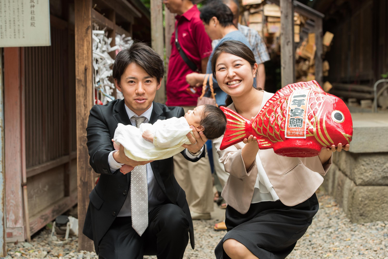 赤ちゃんを掲げるように持つ男性と赤い鯛のオブジェを持った女性