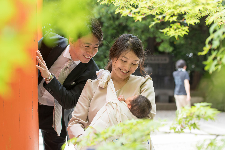 緑の紅葉越しの向こうにいる赤ちゃんを見下ろす女性とのぞき込む男性