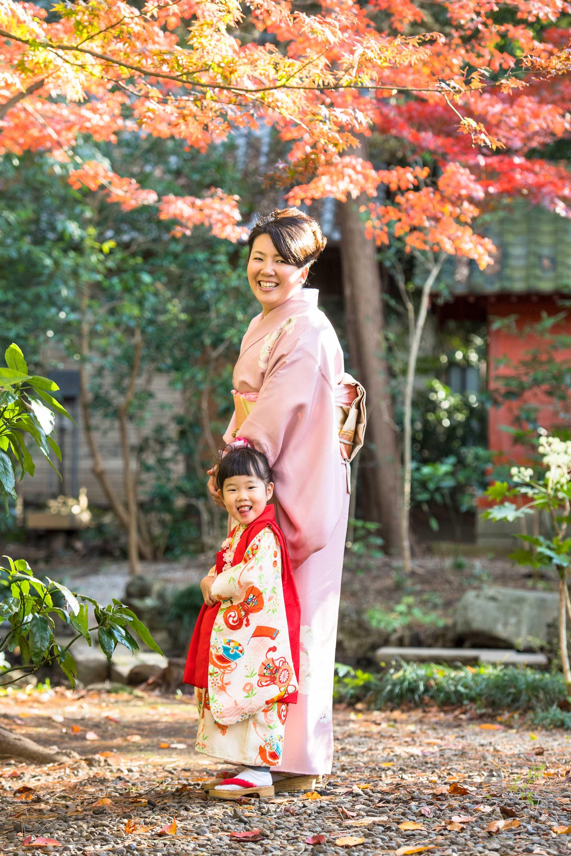 色づくもみじのきの下に立つ七五三の着物姿の女の子と和装のお母さん
