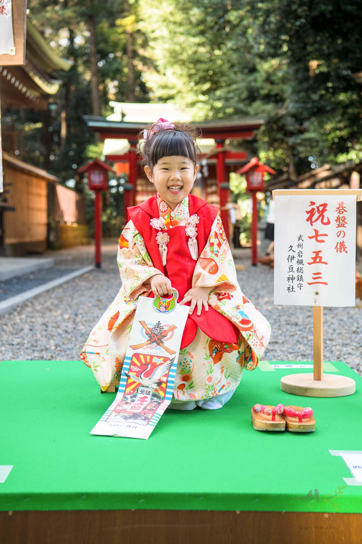 碁盤の上に座り笑顔の七五三の着物姿の女の子