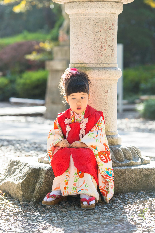 石灯籠の前に座る七五三の着物姿の女の子