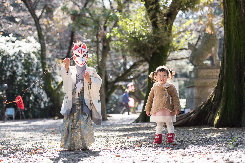狐のお面をつけた七五三の着物姿の男の子と横に立つ小さな女の子