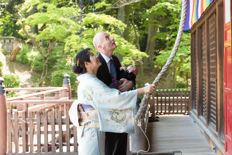 赤ちゃんを抱いた男性と神社の鈴を鳴らしている女性の画像
