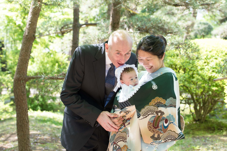 お宮参りの赤ちゃんを抱く和服姿の女性と横に立つ外国人男性の画像