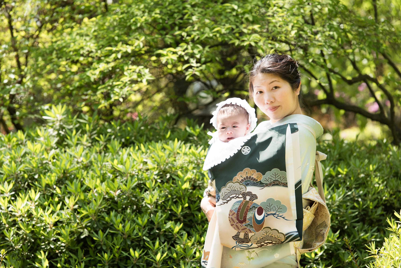 植栽の前に立つ赤ちゃんを抱いた和服姿の女性の画像