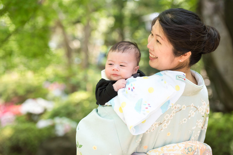 お宮参りの赤ちゃんを抱く和服姿の女性の画像