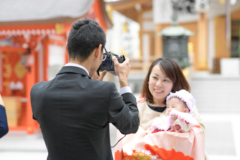 お宮参りの掛着姿の女性に抱かれる赤ちゃんを撮影する男性の後ろ姿