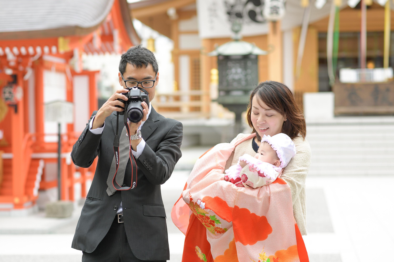 お宮参りの掛着姿の女性に抱かれる赤ちゃんを写真を確認する男性