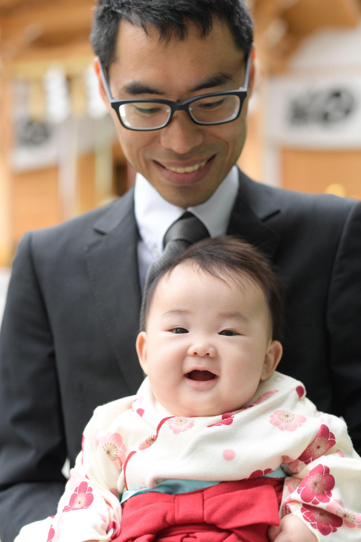 男性に抱かれた笑顔の赤ちゃん
