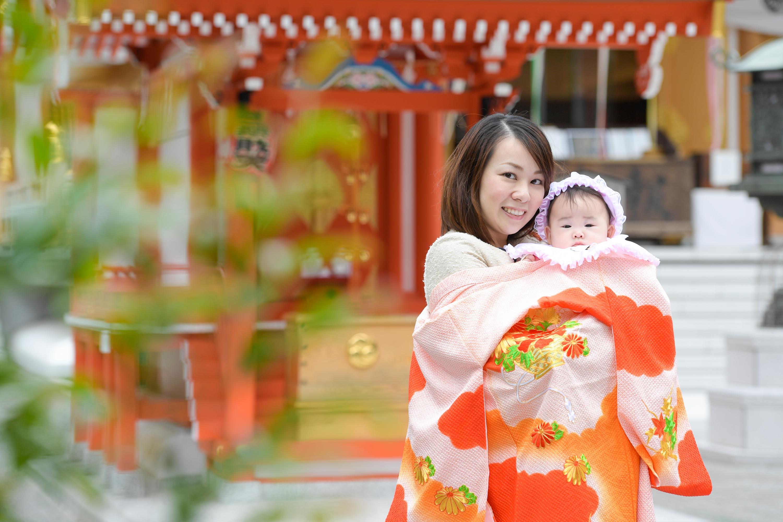 掛着姿の女性に抱かれた赤ちゃん