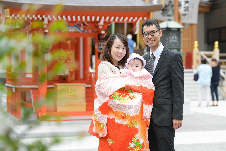 掛着姿の女性に抱かれた赤ちゃんと横に立つ男性