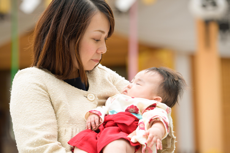 女性に抱かれた赤ちゃんのアップ