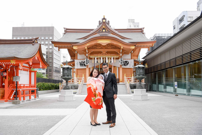 水天宮の本殿をバックにお宮参りの掛着姿の女性に抱かれる赤ちゃんと横に立つ男性