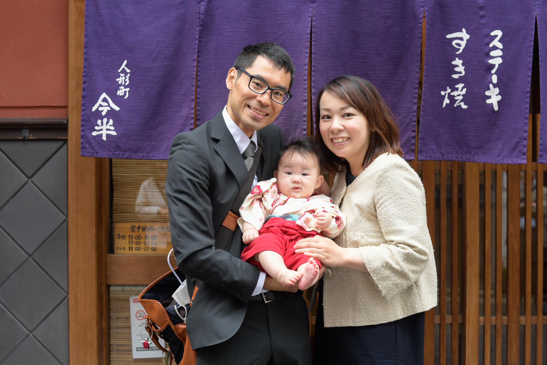 のれんの前に立つ赤ちゃんを抱いた女性と男性