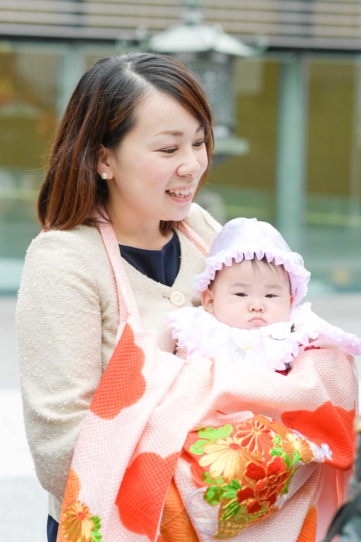 お宮参りの掛着を着た女性に抱かれる赤ちゃん