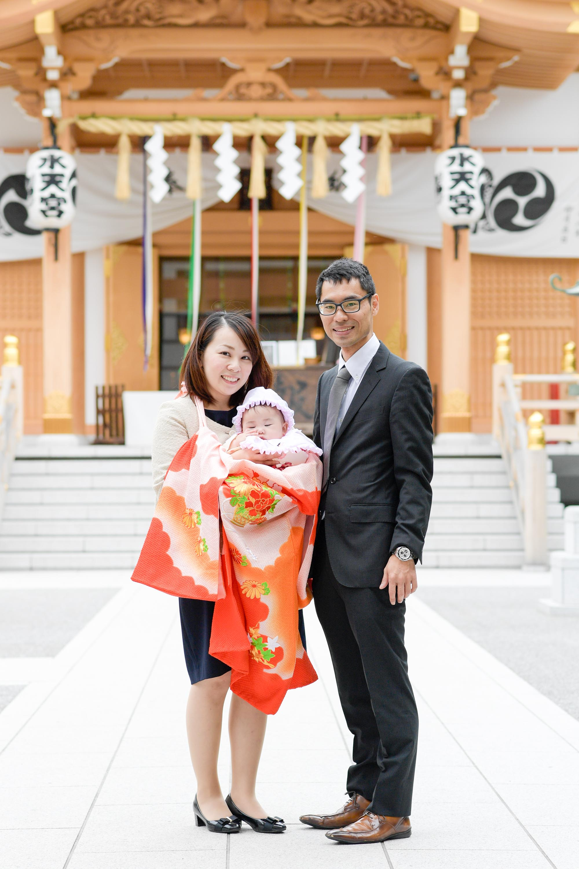 お宮参りの掛着を着た女性に抱かれる赤ちゃんと横に立つ男性